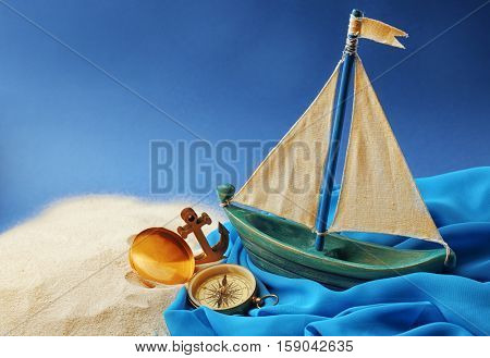 Wooden boat, compass and anchor on blue background. Columbus Day concept