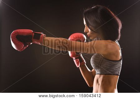 Boxing concept. Boxer woman during boxing exercise making direct hit with red gloves isolated on black background in studio.