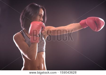 Boxing concept. Profile of fitness or boxer lady with red gloves on practicing direct hits during battle or fight isolated on black background.