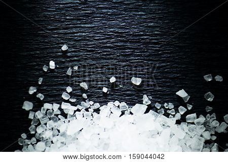 Coarse salt on a dark background. Macro