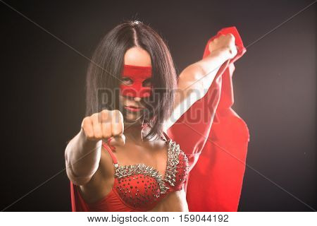 Superwoman. Young pretty woman showing her fist like superhero. Super girl, image toned. Beauty saves world and people.