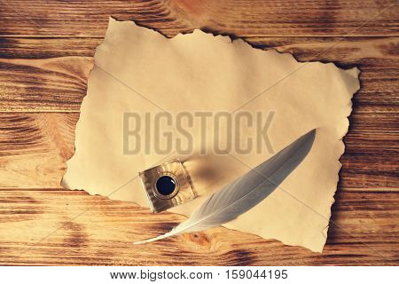 Feather pen with inkwell and sheet of paper on wooden table closeup