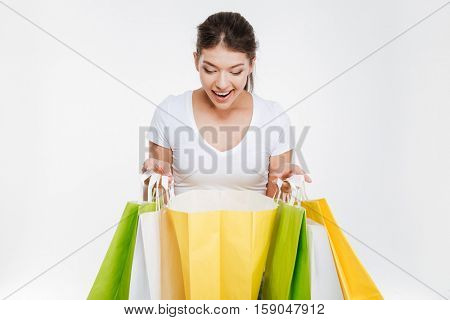 Photo of cheerful young woman holding purchasings after shopping. Isolated over white background. Look down to purchasings.