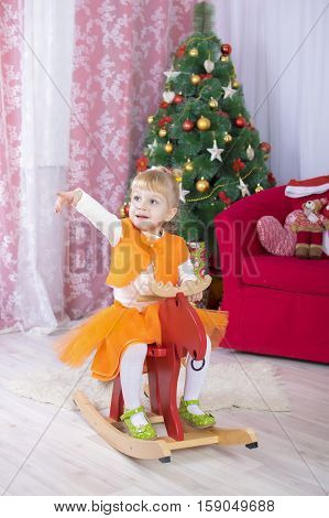 Adorable Little Blonde Girl Sitting On A Toy Horse Near Christmas Tree And Holding A Toy Bear. Prett