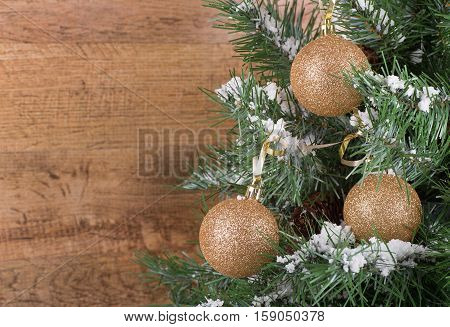 Gold ornaments hanging on a Christmas tree with a wood background