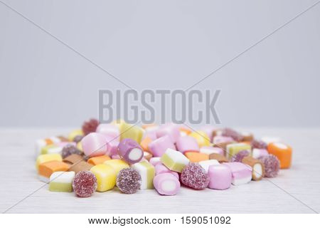 Pile Of Diverse Soft And Chewy Candies On Grey