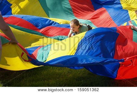 Girl climbing in multi colored billowing parachute
