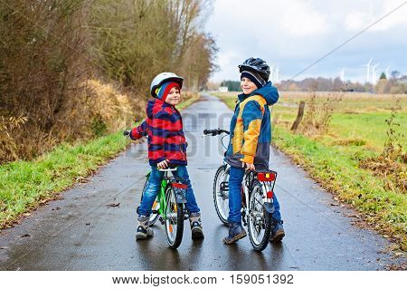 Two active kids boys in helmet biking on bicycles. Happy children in colorful clothes and city traffic. Safety and protection for preschool kids. Friends making sports, acitve leisure.