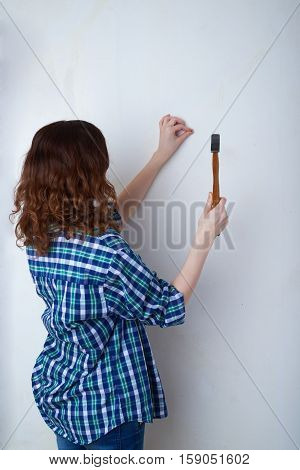 Young woman in casual clothes in front of white unpainted wall working with hammer, happy people and construction concept