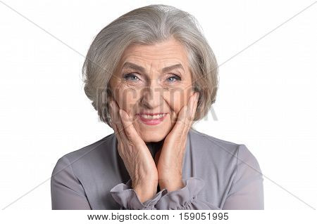 Portrait of smiling senior woman in grey blouse with hands on her cheeks isolated on white background