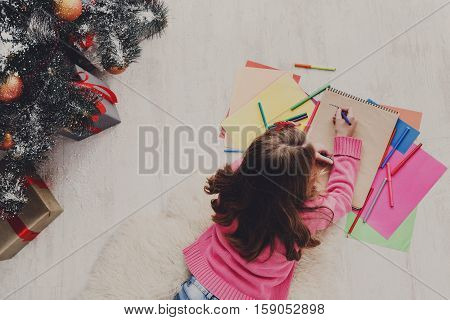 Writing letter to santa. Beautiful girl makes wish list of presents for christmas. Waiting for gift. Prepare for winter holidays, top view of child on floor