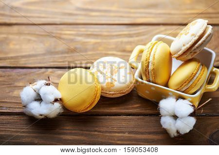 Colorful tasty creme brulee macaroons and orange macaroons in yellow vase with cotton flowers on a wooden table. Soft light. Close view.