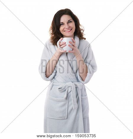 Smiling young woman in bath robe over white isolated background holding ceramic cup in hands, morning, healthy, relaxation and beauty concept