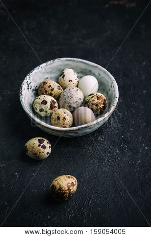 Quail eggs in a bowl on a dark background. Farm products, bio product, food concept, top view.