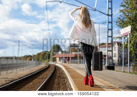 Woman with suitcase waiting in station looking in the far