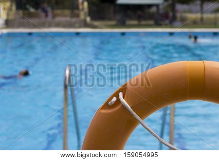 Orange life float. View of pool in the background unfocused.