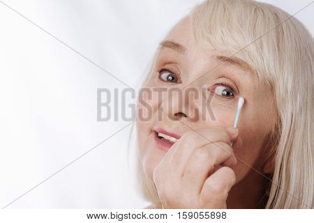 Cotton swabs. Delighted positive aged woman holding a cotton swab and using it while caring about her appearance