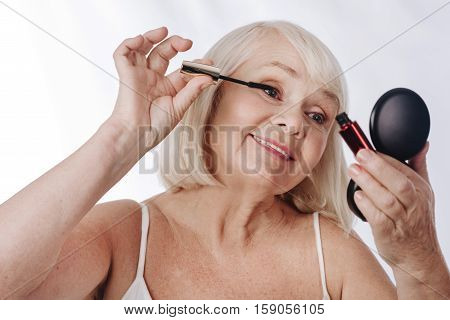 Decorative cosmetics. Good looking content aged woman applying mascara and looking into the mirror while using decorative cosmetics