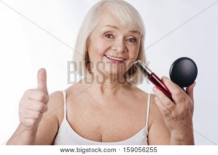 Looking younger. Delighted positive senior woman holding mascara and showing thumb up while enjoying make up
