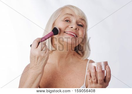 Beauty tools. Happy nice senior woman using a cosmetic brush and applying face powder while concealing skin imperfections