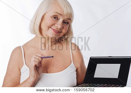 Beautiful eyes. Nice delighted elderly woman holding an eyeshadow palette and smiling while putting on eyeshadow