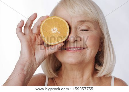 Citrus energy. Nice elated senior woman standing against the white background and smiling while putting an orange half to her eye