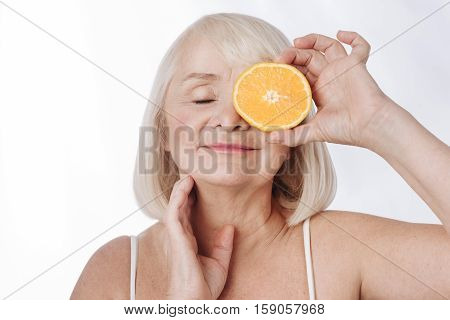 Citrus facial mask. Pleasant charming grey haired woman holding an orange half and closing her eyes while using oranges for cosmetic purposes
