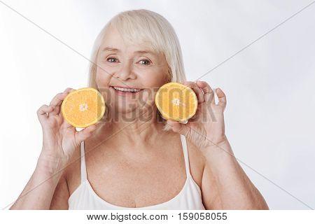 Two orange halves. Joyful charming senior woman holding two orange halves and smiling while standing against the white background
