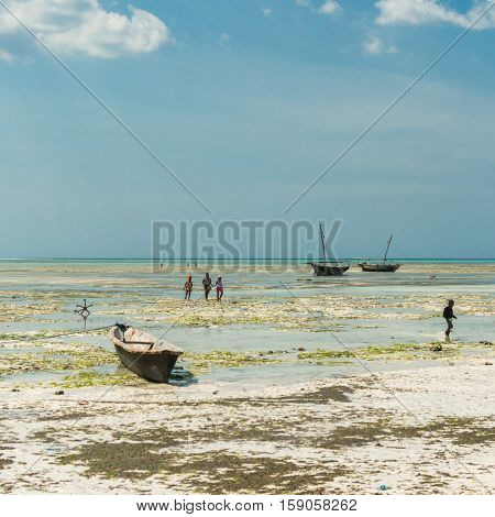 ZANZIBAR, TANZANIYA- JULY 10: children playing on the shallow near fishing boats on July 10, 2016 in Zanzibar
