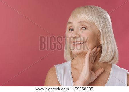 Feeling young. Smiling content elderly woman holding her hand up and touching her neck while feeling young