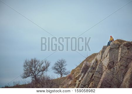 lonly man on a cliff in clod autumn wather