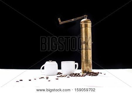 two empty coffee cups, coffee mill and coffee seeds