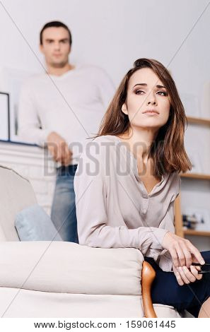 It was a hard week. Pleasant gloomy beautiful woman sitting in the arm chair and feeling exhausted while her husband standing in the backgound