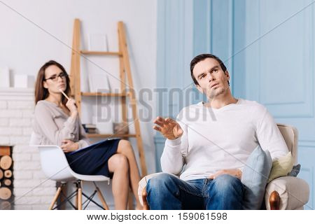Reveal your thoughts. Pleasanttal talkative handsome man sitting in the armchair and discussing his problems while professional psychologist sitting in the background