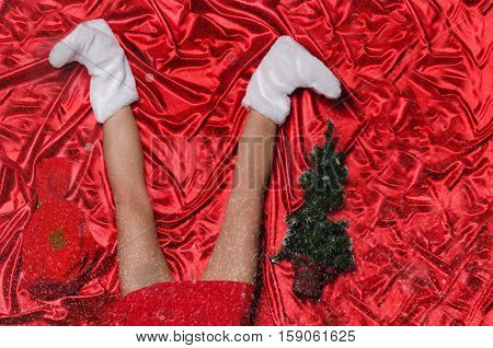 Beautiful female legs with snowflakes and Christmas tree on red background
