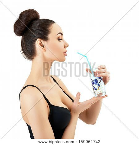 Portrait of beautiful woman drinks beauty cocktail, profile. silhouette of attractive girl holding glass with pills in studio over gray background with copy space. Beauty and antiaging concept.