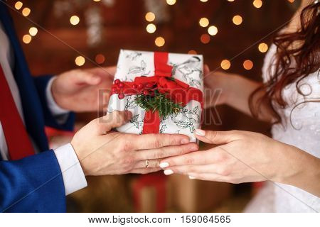Hands of bride and groom holding giftbox with red ribbon, christmas gift. Winter wedding