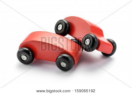 Two stylized toy wooden red cars pile on one another conceptual of a motor vehicle accident or collision on white with copy space