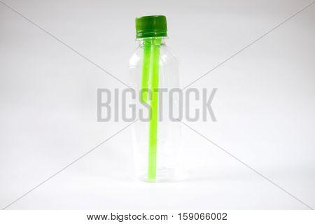 plastic bottle of water green straws inside on white