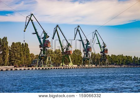 Port cranes for unloading sand on ship.
