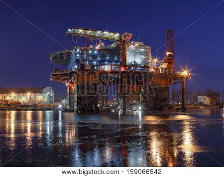 Oil rig under construction at night in Gdansk Poland.