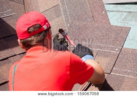 Roofer builder worker installing shingles on a new wooden roof with skylight using hammer
