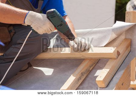 Skylight installation. Roofer builder worker use skrewdriver to fasten a wooden beam