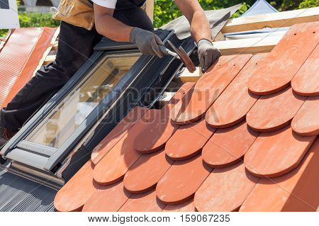 Hands of roofer laying tile on the roof. Installing natural red tile using hammer