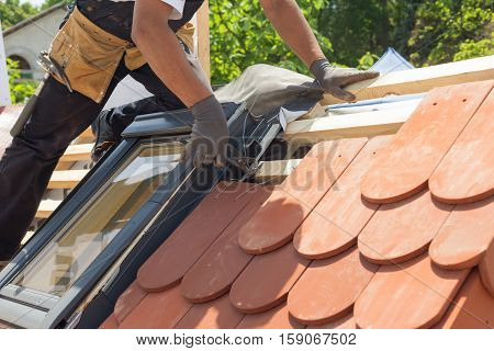 Hands of roofer laying tile on the roof. Installing natural red tile using pliers. Roof with mansard windows. poster