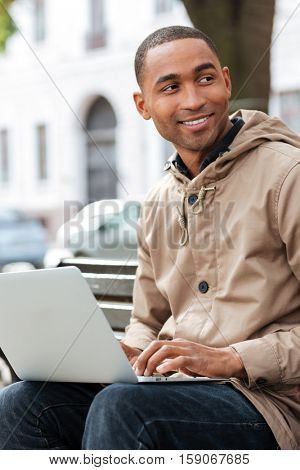 Image of young african cheerful man with laptop sitting on a wooden bench and typing. Look aside.
