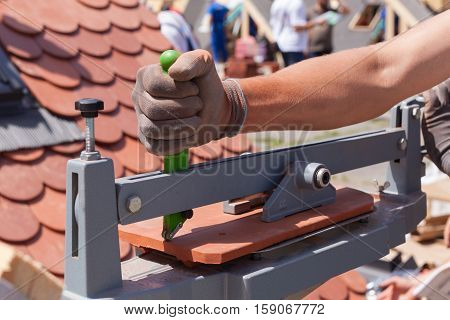Roofer builder worker use tile cutter to create a correct size of natural red ceramic tile