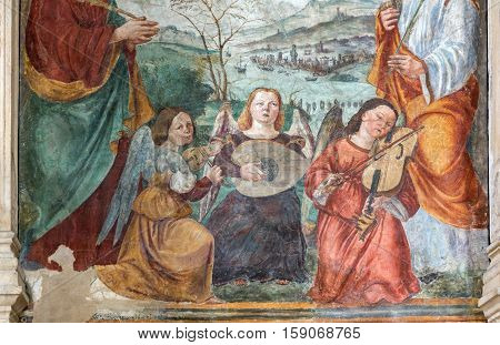 PADUA, ITALY - MAY 3, 2016: The fresco of angels with the music instruments by Bonino da Campione in the church of The Eremitani as the detail of on tomb of Umberto da Carrara. Padua Italy