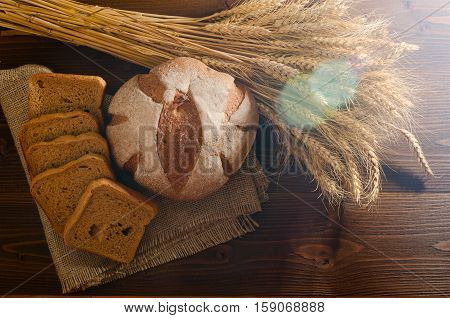 Round rye bread on sacking and a sheaf in the sunlight solar glare. Wooden background top view