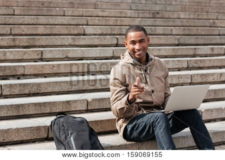 Picture of young african happy man sitting on staircase and using laptop while pointing at camera. Looking at camera.